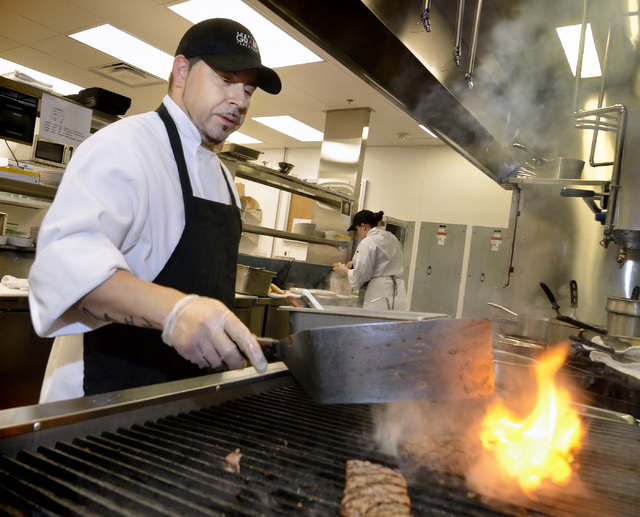 Tony Lagunas grills a hamburger and steak in the kitchen of the Stewart + Ogden diner bistro in the Downtown Grand hotel-casino. (Bill Hughes/Las Vegas Review-Journal)