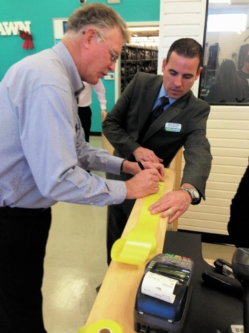 Henderson Mayor Andy Hafen, left, signs a ceremonial ribbon with the assistance of John Carlisle, SuperPawn market manager, during the grand reopening of the 1100 W. Sunset Road SuperPawn. The com ...