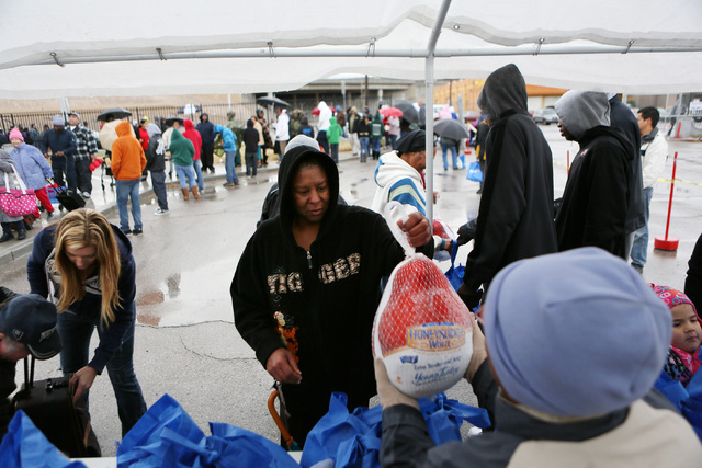 Jackie Smith, center, receives a frozen turkey from a volunteer during the Las Vegas Rescue Mission turkey and food basket giveaway event located at the old Moulin Rouge property at 900 W. Bonanza ...