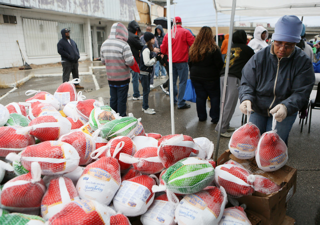 Volunteer Vickie Riley, right, organizes frozen turkeys during the Las Vegas Rescue Mission turkey and food basket giveaway event located at the old Moulin Rouge property at 900 W. Bonanza Road Sa ...