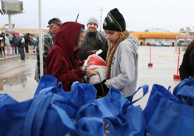 Veronica Arbis, center left, receives a frozen turkey from Shawna Hoge, center right, during the Las Vegas Rescue Mission turkey and food basket giveaway event located at the old Moulin Rouge prop ...