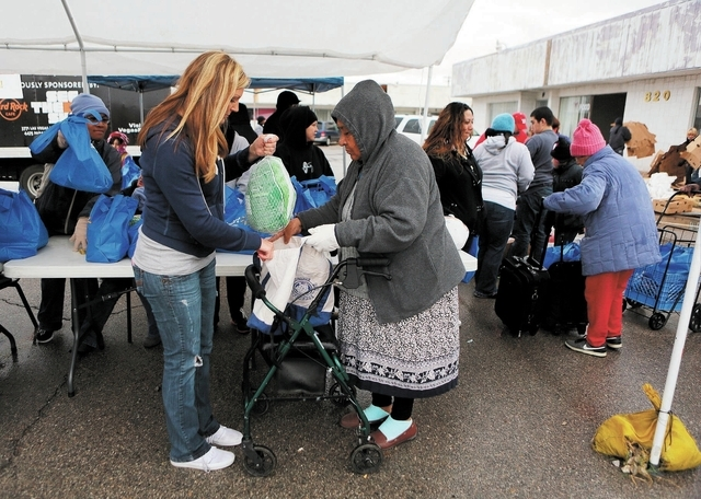 Nicole Camp, left, gives a woman, who declined to give her name, a frozen turkey during the Las Vegas Rescue Mission turkey and food basket giveaway event located at the old Moulin Rouge property  ...