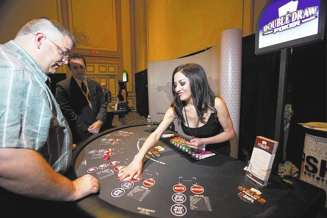 Darin Cummins, left, plays Double Draw Poker at the SHFL Entertainment booth with dealer Candida Duenas on Tuesday at the Table Games Conference at Paris Las Vegas. (Samantha Clemens/Las Vegas Rev ...
