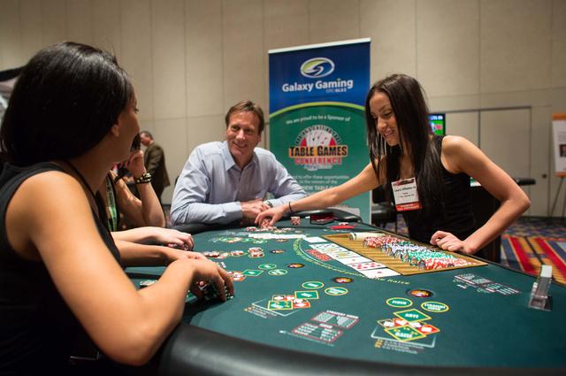 Lemon Mosissa, left, Dean Barnett and Laura Villanueva play High Card Flush on Tuesday at Galaxy Gaming's booth at the Table Games Conference at Paris Las Vegas. A growing table games market att ...
