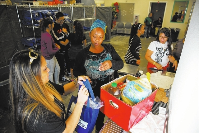Volunteer Rita Arriola, left, hands Anita Morgan a bag containing rolls and pumpkin pie on Monday at Catholic Charities of Southern Nevada, 1501 Las Vegas Blvd. North. Clients of Catholic Charitie ...