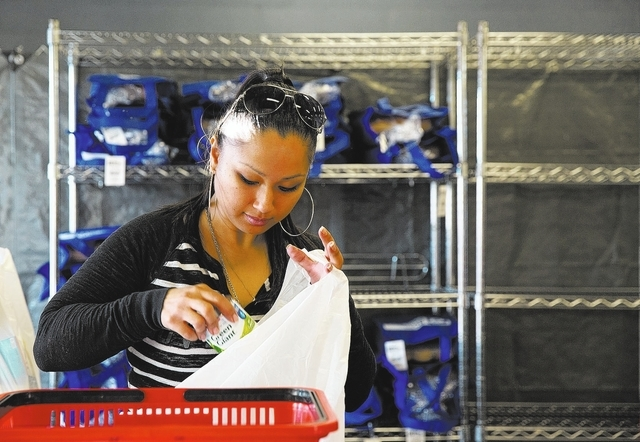 Volunteer Renee Terry packs food for a Catholic Charities of Southern Nevada client on Monday. Catholic Charities clients are able to receive a free turkey and side dishes through Thanksgiving Day ...