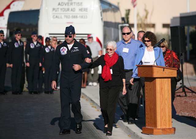 Lt. Col. Greg Moseley (CQ) left, escorts Shirley Buckley, center, during the start of a rededication ceremony for Buckley's late husband Capt. Gene Devlin outside the Thunderbirds Hangar at Nellis ...