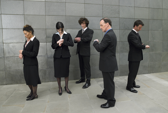Business people checking watches in street