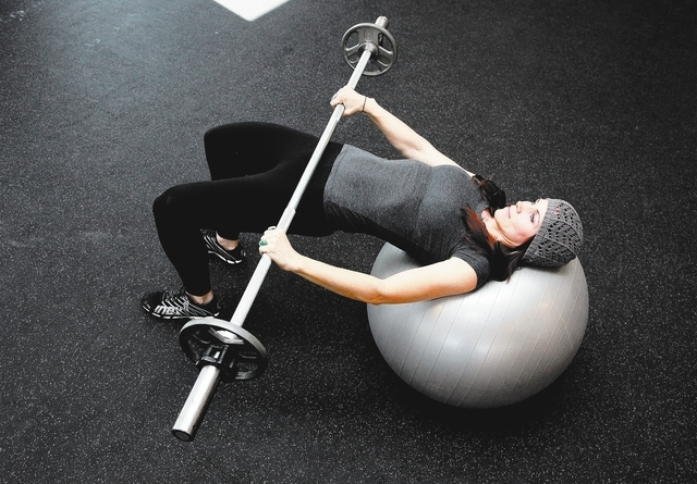 Trainer Laura Salcedo demonstrates the finishing position for the stability ball weighted hip raise at Mountains Edge CrossFit in Las Vegas on Tuesday, Oct. 29, 2013. (Justin Yurkanin/Las Vegas Re ...