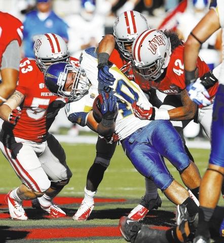 Jarrod Lawson of San Diego State gets tackled by UNLV during their football game at Sam Boyd Stadium in Las Vegas Saturday, Nov. 2, 2013. (John Locher/Las Vegas Review-Journal)