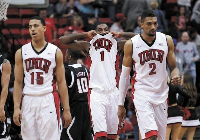 UNLV freshman point guard Kendall Smith (15) joins forward Roscoe Smith (1) and guard Khem Birch in a sigh of relief after the Rebels' 73-70 victory over Omaha on Nov. 15 at the Thomas & Mack Ce ...
