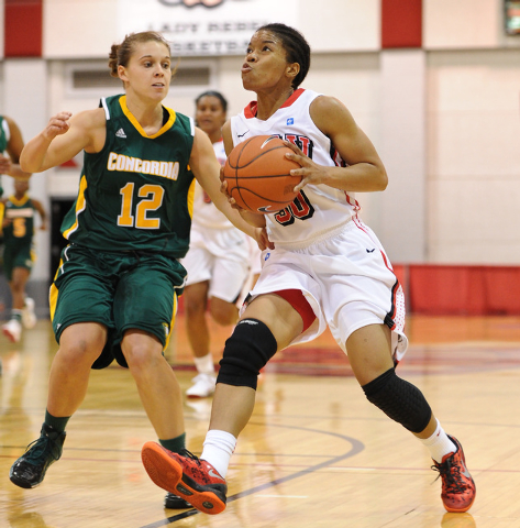 UNLV's Mia Bell (30) drives past Concordia defender Carly Bishop (12) during an exhibition basketball game at the Cox Pavilion in Las Vegas Monday, Nov. 4, 2013. (David Cleveland/Las Vegas Review- ...