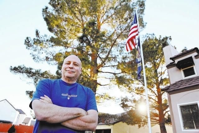Las Vegas USO volunteer Jack Ross stands outside his patriotically decorated home Monday, Nov. 25, 2013, in Las Vegas. Ross is unhappy to learn that the USO's national director earned $559,401 in  ...