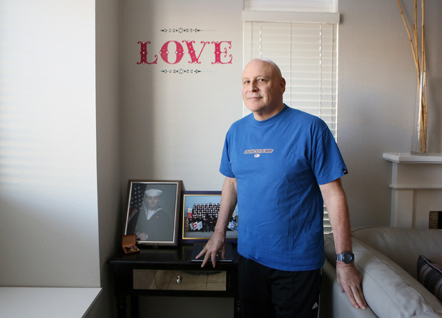 Las Vegas USO volunteer Jack Ross stands near a photo of his enlisted son at Rossՠhome Monday, Nov. 25, 2013, in Las Vegas. Ross is unhappy to learn that the USO's national director earned $ ...