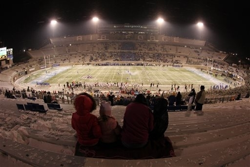 Fans huddle together in the near-empty stands as UNLV kicks off to Air Force in the first quarter of an NCAA football game at Air Force Academy, Colo., on Thursday, Nov. 21, 2013. (AP Photo/David  ...