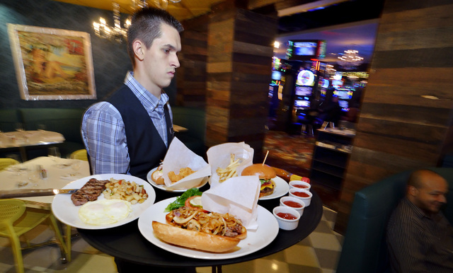 Waiter Teylan Stephens takes food to a table at the Stewart + Ogden diner bistro in the Downtown Grand hotel-casino. (Bill Hughes/Las Vegas Review-Journal)
