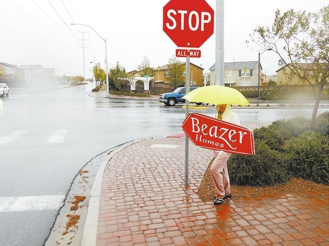 Sign spinner Maaret Easley, 46, mans a busy street corner at Centennial Hills' Knickerbocker Park on a rainy Nov. 23, 2013. Easley, pictured at the corner of Shaumber Road and West Dorrell Lane, w ...