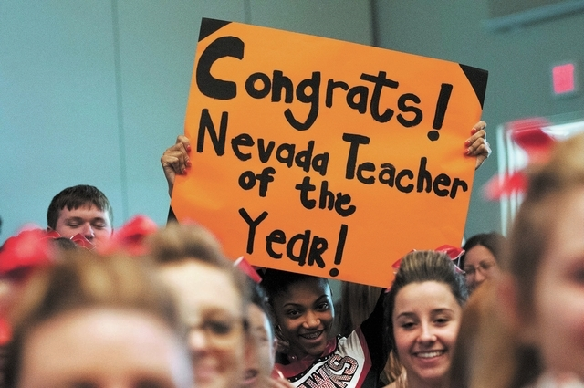 Student Gianna Bates, center, holds a sign congratulating her school's teacher Jeffrey A. Hinton, during a ceremony honoring him as the Nevada Teacher of the Year at Northwest Career and Technical ...