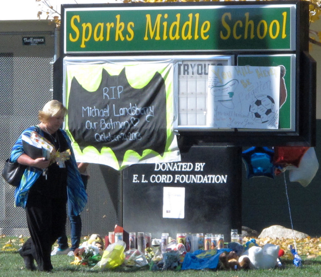 Washoe County School Board President Barbara Clark walks past a makeshift memorial in front of Sparks Middle School on Oct. 23. Math teacher Michael Landsberry was killed and two students wounded  ...