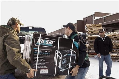 Family Farm & Home of Mason employees and Dean Haynes, left, and Bobby Hollon load a generator into Nathan Timm's truck, Tuesday, Dec. 24, 2013. Timm, of Ovid, was buying the generator for his par ...