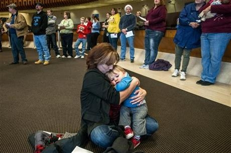 "Carla Coulter, 46, of Clio, holds her 1-year-old grandson Connor Hergert closely as she gives him a kiss on the forehead while listening to the FirstMerit Bank Mixed Chorus sing ""Silent Night"" alo ..."