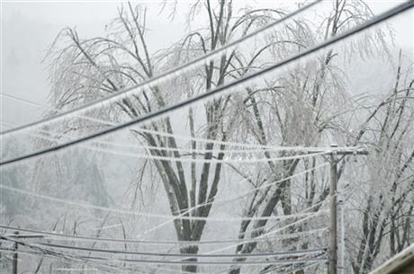 Trees and power lines grow heavy with ice as freezing rain continues into Monday morning, Dec. 23, 2013, in Cambridge, Vt. From Michigan to Maine, hundreds of thousands remain without power days a ...