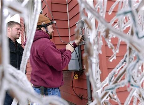 Jake Baldino, left, and Mick Benbow of K & T Electric of DeWitt replace an electrical box and pole to a home in DeWitt Township, Mich., Monday, Dec. 23, 2013. From Michigan to Maine, hundreds of t ...