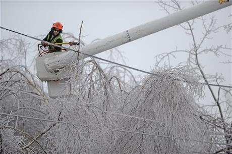Andrew Powers, an arborist with Asplundh Tree Experts, clears iced branches from power lines along Mayflower Heights Drive in Waterville, Maine, on Monday, Dec. 23, 2013. Central Maine Power said  ...