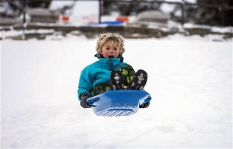 Samson Boldizar, 8, goes airborne as he toboggans near the Arboretum on Christmas Day in Ottawa, Canada, on Wednesday, Dec. 25, 2013. (AP Photo/The Canadian Press, Justin Tang)