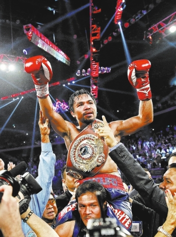 Manny Pacquiao from the Philippines wears the champion's belt after defeating Brandon Rios of the United States in their WBO international welterweight title fight Sunday, Nov. 24, 2013, in Macau. ...