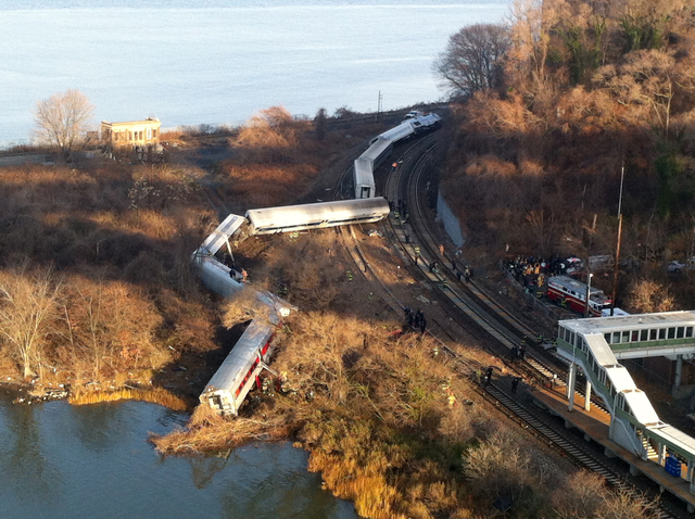 """Cars from a Metro-North passenger train are scattered after the train derailed in the Bronx neighborhood of New York, Sunday, Dec. 1, 2013. The Fire Department of New York says there are """"mul ..."""