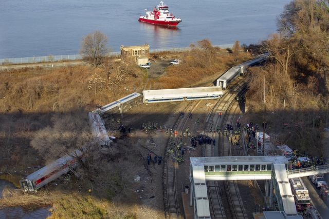 A New York Fire Department boat approaches the scene of a Metro-North passenger train in the Bronx borough of New York Sunday, Dec. 1, 2013. The train derailed on a curved section of track early S ...