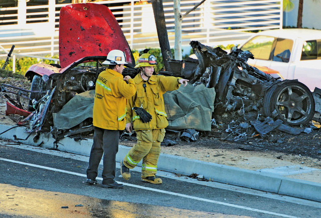 First responders gather evidence near the wreckage of a Porsche sports car that crashed into a light pole on Hercules Street near Kelly Johnson Parkway in Valencia on Saturday, Nov. 30, 2013. A pu ...