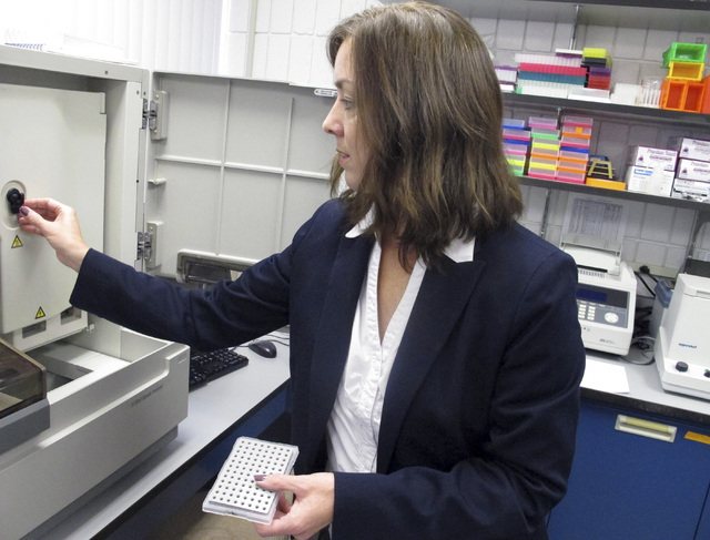 Heather Miller Coyle, an associate professor at the University of New Haven, shows a DNA sequencer in a school laboratory in West Haven, Conn. (AP Photo/Dave Collins)
