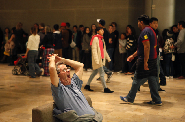 A man, who declined to give his name, yawns and stretches out while waiting in a chair as hundreds wait in line to shop at Urban Outfitters in the Fashion Show mall in Las Vegas early in the morni ...