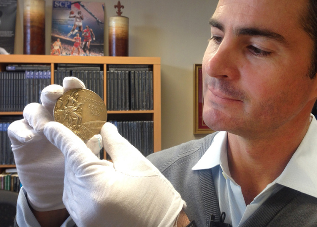 In this Nov. 19, 2013 photo, Dan Imler of SCP Auctions shows Jessie Owens gold medal from the 1936 Olympics at the SCP Auctions in Laguna Nigel, Calif. One of the four Olympic gold medals won by t ...