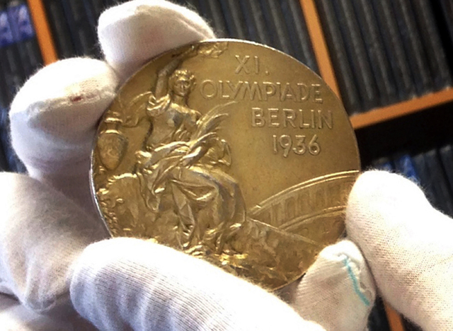 This Nov. 19, 2013 photo shows track and field star Jesse Owens' gold medal is displayed from his 1936 Olympics win at the SCP Auctions in Laguna Nigel, Calif. One of the four Olympic gold medals  ...