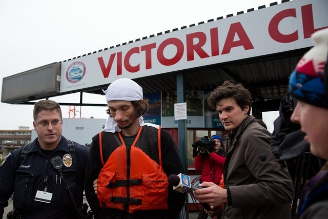 A police officer escorts Samuel Kenneth McDonough, wearing a white cloth on his head, who is a suspect in commandeering a Victoria Clipper after it was found adrift in Elliot Bay in Seattle on Sun ...