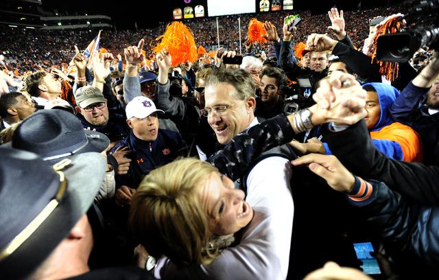Auburn head coach Gus Malzahn celebrates with his wife Kristi after their 34-28 win over No. 1 Alabama in an NCAA college football game, Saturday, Nov. 30, 2013, at Jordan-Hare Stadium in Auburn,  ...