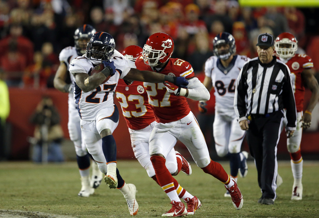 Denver Broncos running back Knowshon Moreno (27) runs against Kansas City Chiefs cornerback Sean Smith (27) during the second half on Sunday in Kansas City, Mo. The Broncos won 35-28. (AP Photo/Or ...