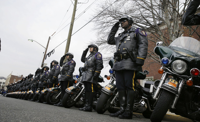 A row of motorcycle police officers from towns around northern New Jersey salute during services for Michael Feeney, as Ridgewood, N.J., holds a funeral with full police honors for the 10-year-old ...