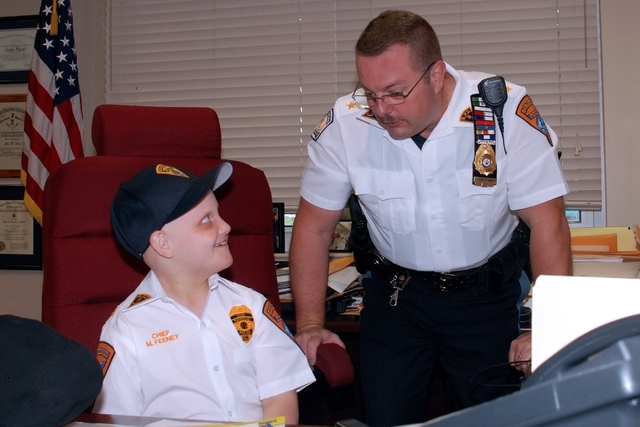 In this photo taken on June 14, 2013,  honorary Ridgewood, N.J., Police Chief Michael Feeney, left, 10, gets some advice from Ridgewood Police Chief John Ward at the start of the work day in Ridge ...