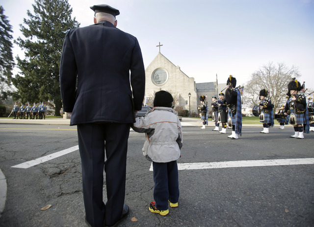 A police officer holds his son's hand outside a church during the funeral for Michael Feeney Tuesday, Dec. 3, 2013, in Ridgewood, N.J. Feeney, 10, was named Ridgewood's honorary police chief for 2 ...