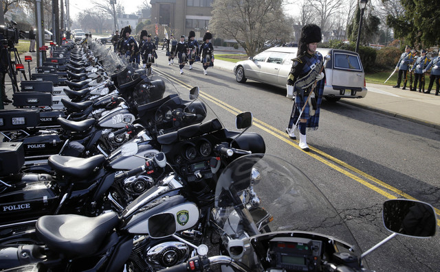 A pipe and drum band march past a row of police motorcycles during a procession for Michael Feeney, as Ridgewood, N.J., holds a funeral with full police honors for the 10-year-old boy, Tuesday, De ...