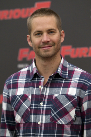 "FILE - In this April 29, 2011 file photo, actor Paul Walker poses during the photo call of the movie "" Fast and Furious 5,"" in Rome.  Walker was drawing parallels before his untimely dea ..."