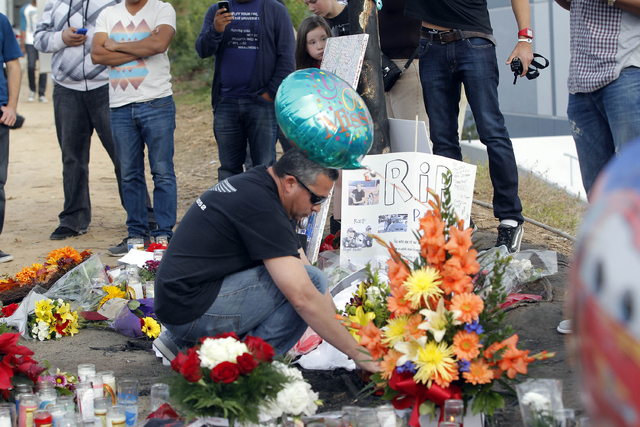 A man views flowers and memorials at a roadside memorial at the site of the auto crash that took the life of actor Paul Walker and another man, in the small community of Valencia, Calif., Monday,  ...