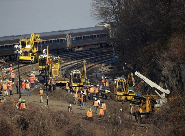 A train passes by the scene of repair efforts at the site of a train derailment in the Bronx borough of New York, Tuesday, Dec. 3, 2013.  The National Transportation Safety Board says right now, i ...