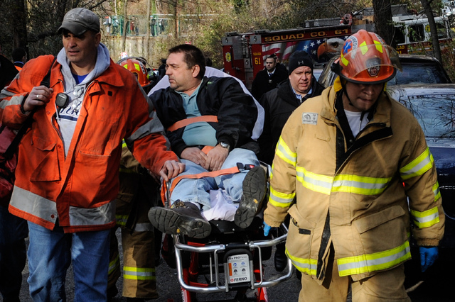 In this photo taken on Sunday, Dec. 1, 2013, Metro North Railroad engineer William Rockefeller is wheeled on a stretcher away from the area where the commuter train he was operating derailed in th ...