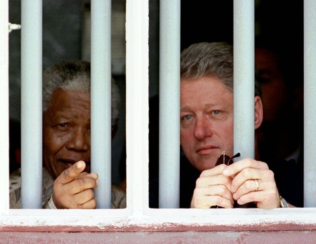 South African President Nelson Mandela, left, and U.S. President Bill Clinton peer through the bars of prison cell No. 5, the cramped, gray cell where Mandela was jailed for 18 years in his strugg ...