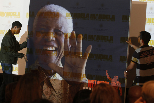 "A giant poster of Nelson Mandela is moved to center stage at a news conference on Nov. 2 to promote the newly released film ""Mandela: Long Walk To Freedom,"" in Johannesburg. Mandela died Thursday  ..."